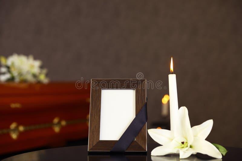 Schwarzer Fotorahmen mit brennender Kerze und weiße Lilie auf Tabelle lizenzfreies stockfoto