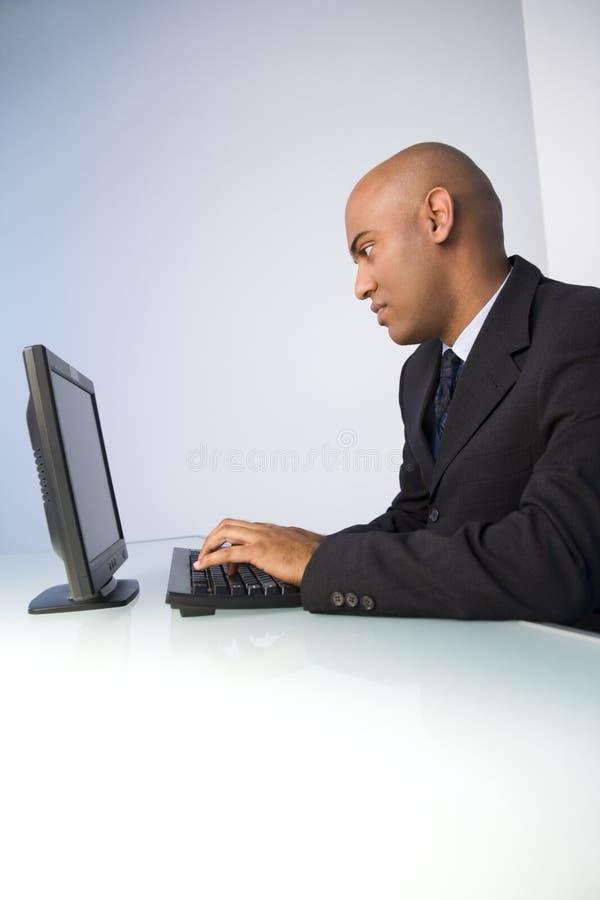 Schwarzer Geschäftsmann auf Computer stockbilder