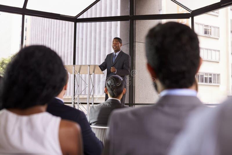 Schwarzer Geschäftsmann, der Geschäftsseminar einem Publikum darstellt lizenzfreie stockfotos