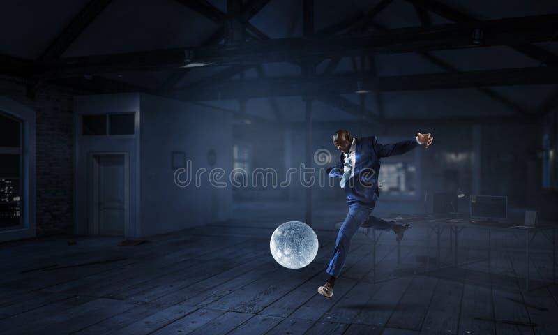 Schwarzer Geschäftsmann spielt Fußball mit Mond lizenzfreies stockbild