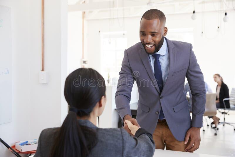 Schwarzer Geschäftsmann und Sitzfrau, die Hände im Büro rüttelt lizenzfreie stockfotografie