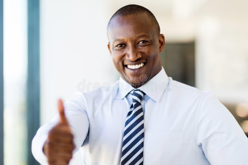 Schwarzer Geschäftsmanndaumen oben stockfoto