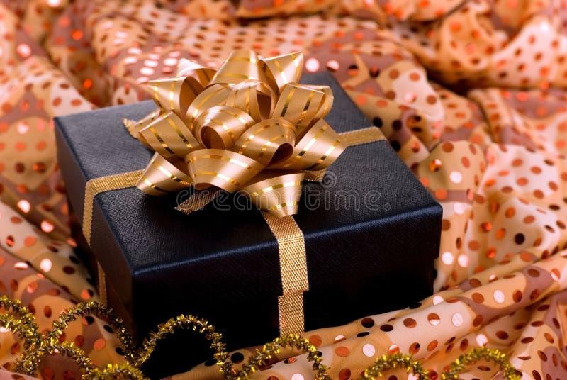 Schwarzer Geschenkkasten mit Goldfarbband. stockbild