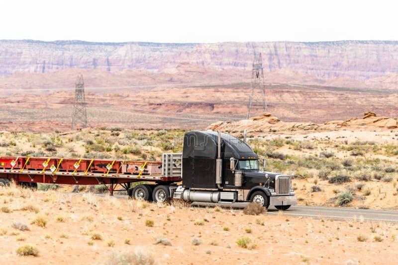 Schwarzer großer LKW der Anlage halb transportiert radioaktive Substanzen in den Behältern, die halb am Anhänger des Flachbetts a lizenzfreies stockbild
