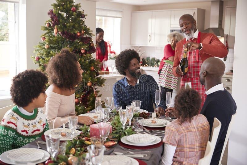 Schwarzer großväterlicher öffnender Champagner für seine multi Generationsfamilie, erfasst im Esszimmer für Weihnachtsessen stockbild