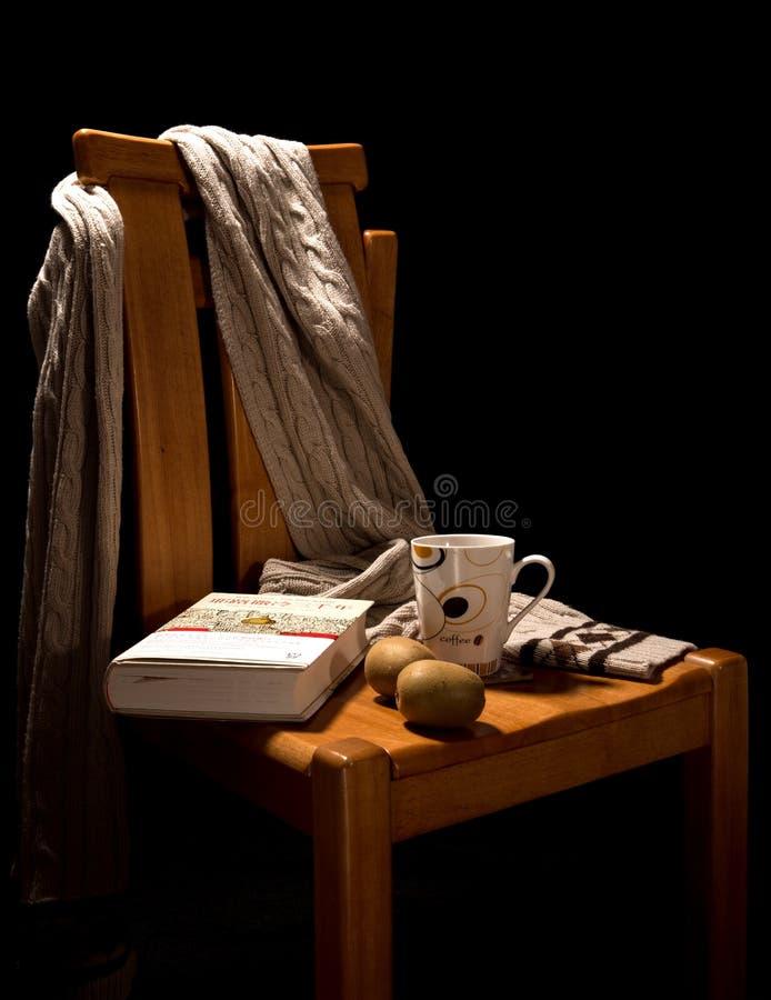 Schwarzer Hintergrund, Holzstuhl für das Ablesen unter dem warmen Licht-, Teetasse-, Buch-, Frucht- und Wollschal, Szene lesend,  lizenzfreies stockbild
