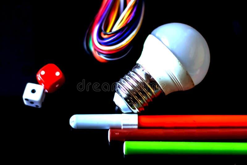 Schwarzer Hintergrund mit Glühbirne, Kabeln, Farben und Muttern stockfotografie