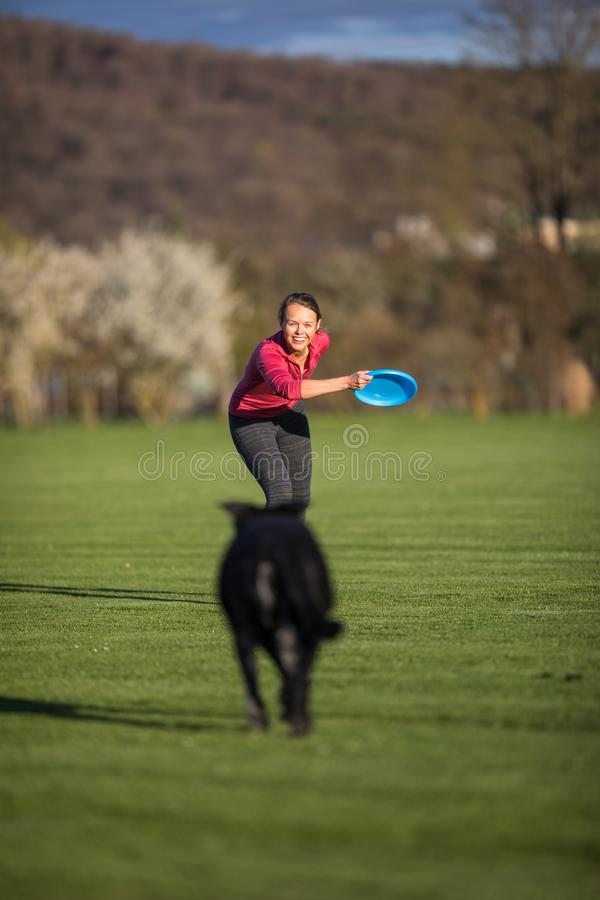 Schwarzer Hund, der schnell draußen, spielend mit Frisbee läuft stockfoto