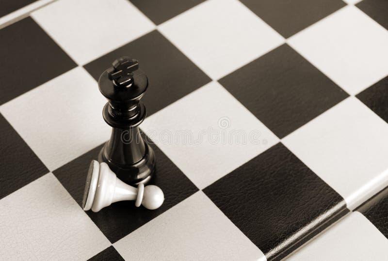 Schwarzer König gewinnt weißes Pfand stockbild