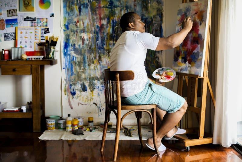 Schwarzer Künstlermann, der sein Kunstwerk erledigt lizenzfreie stockbilder