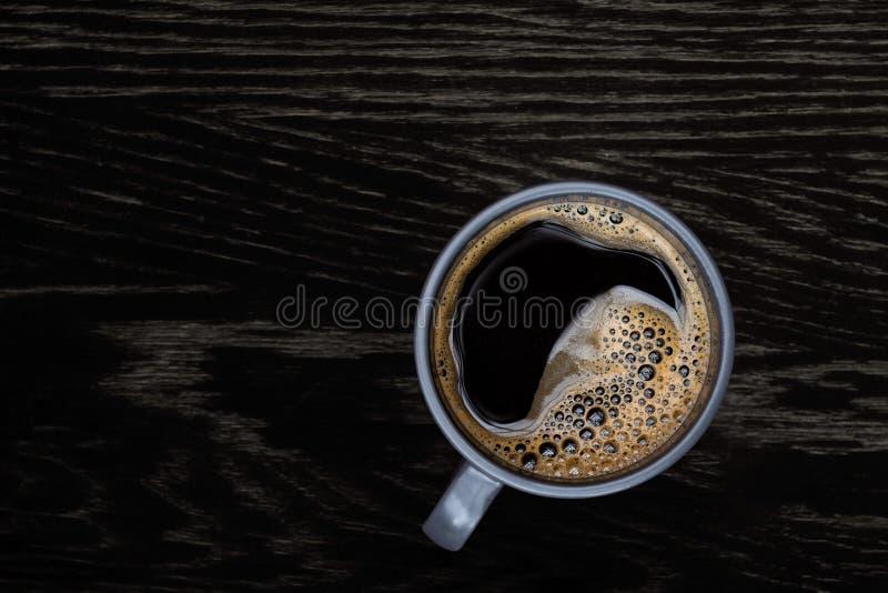 Schwarzer Kaffee in einem blau-grauen keramischen Becher lokalisiert auf dunkelbrauner hölzerner Tabelle mit Korn von oben Raum f stockfotografie
