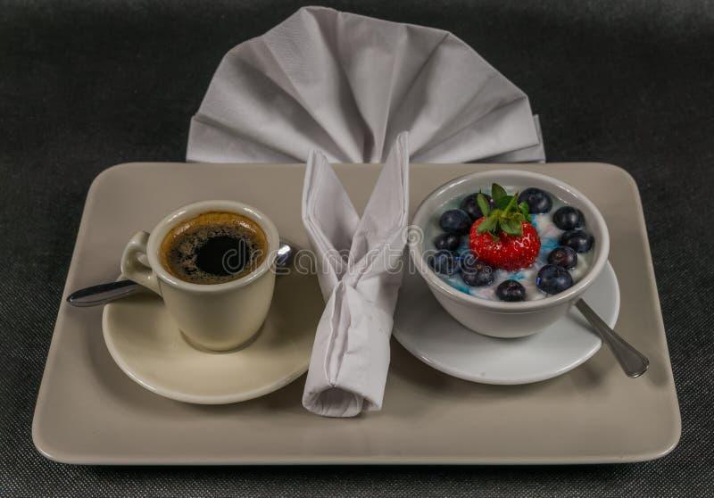 Schwarzer Kaffee in einer Cremeschale, Nachtisch, Jogurt mit einem großen strawb lizenzfreies stockbild
