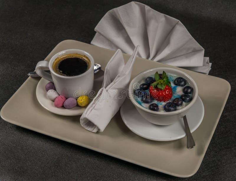 Schwarzer Kaffee in einer Cremeschale, Nachtisch, Jogurt mit einem großen strawb stockfotografie