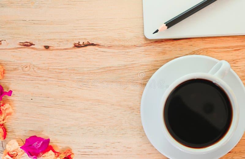 Schwarzer Kaffee im weißen Glas und im Bleistift auf Buch auf Holztischhintergrund stockfoto