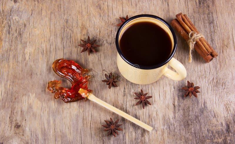 Schwarzer Kaffee und Gewürze in der Becheremaillierung und ein Lutscher in Form eines Hahns stockbilder