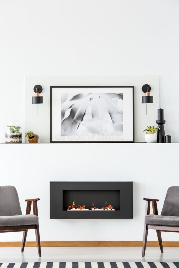 Schwarzer Kamin zwischen grauen Lehnsesseln in weißen flachen Innenraum wi stockbild