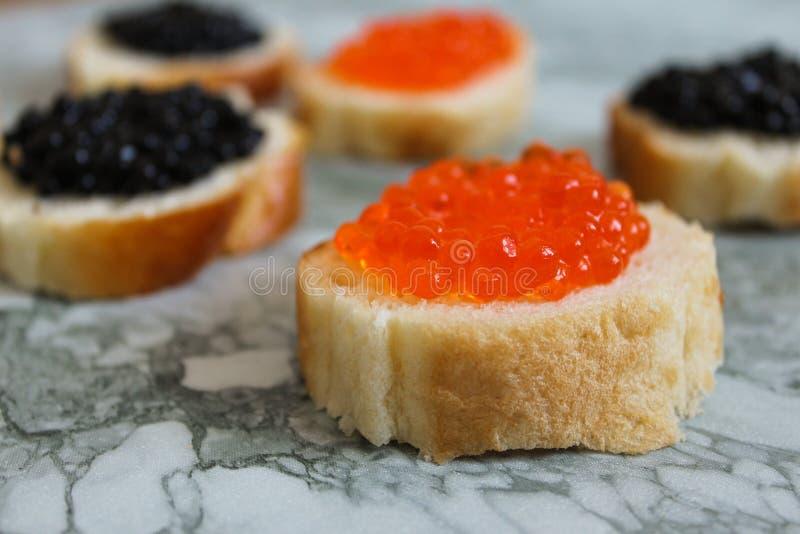 Schwarzer Kaviar Luxuriöse kulinarische Zartheit Nahaufnahmelachskaviar Meeresfrüchte Roter Kaviarnahaufnahmehintergrund stockfotos