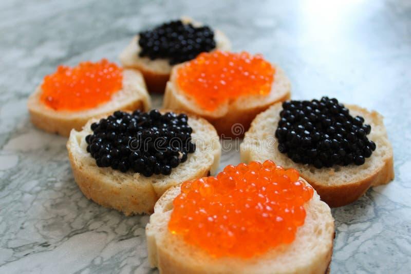 Schwarzer Kaviar Luxuriöse kulinarische Zartheit Nahaufnahmelachskaviar Meeresfrüchte Roter Kaviarnahaufnahmehintergrund lizenzfreie stockfotos