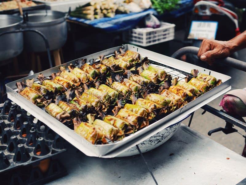 Schwarzer klebriger Reis mit Kokosmilch und die Wasserbrotwurzel, die in der Banane eingewickelt wird, treiben Blätter stockbilder