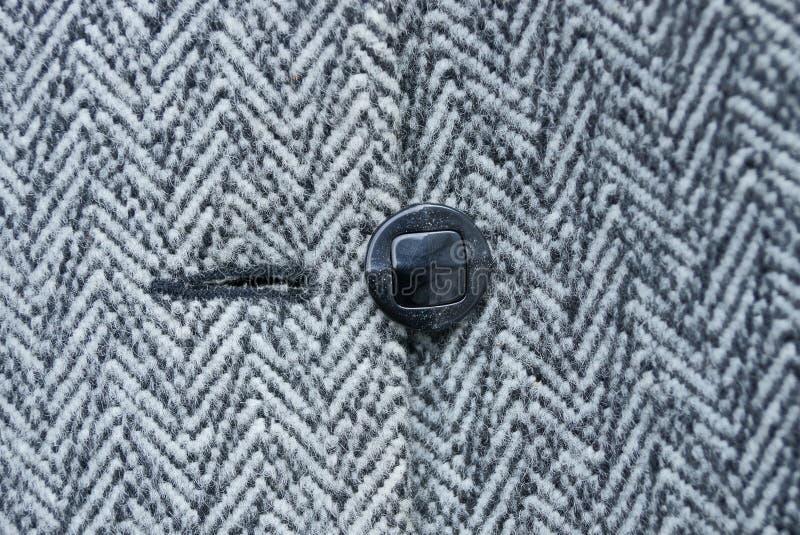Schwarzer Knopf auf woolen gestreifter woolen Kleidung lizenzfreies stockbild