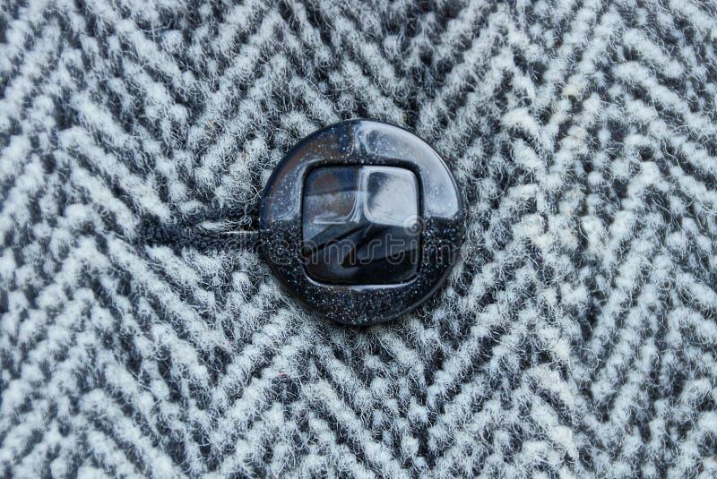 Schwarzer Knopf auf woolen gestreifter woolen Kleidung stockbilder