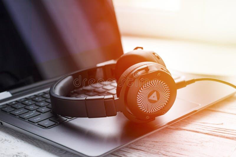 Schwarzer Kopfhörer und Laptop-Computer lizenzfreies stockbild