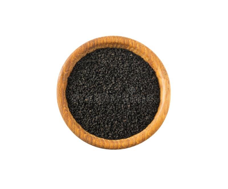 Schwarzer Kumin isoliert auf weißem Grund Oberansicht Schwarzer Kumpensamen in einer Holzschüssel auf weißem Grund isoliert Saatg stockbild