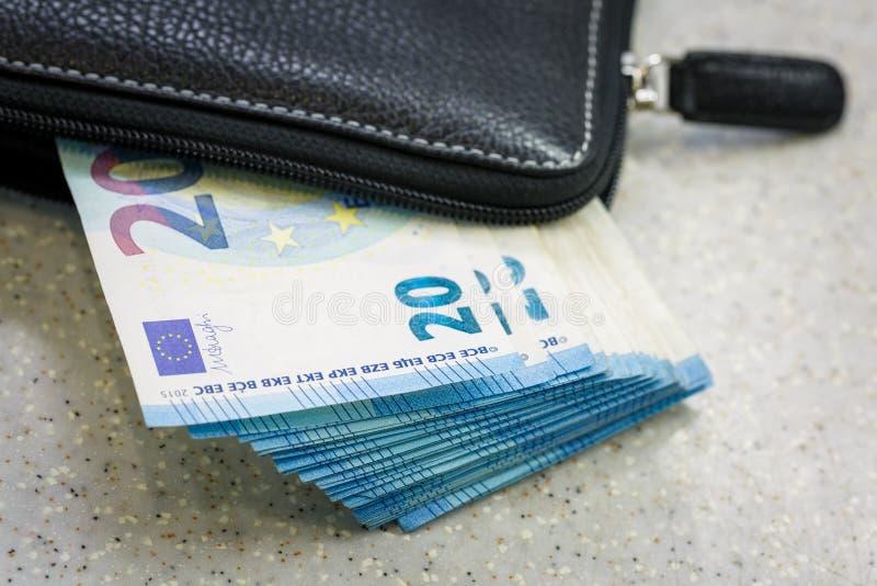 Schwarzer lederner Geldbeutel und Pack des Bargeldes 20 Euros sind Lüge auf der grauen Tabelle stockbild