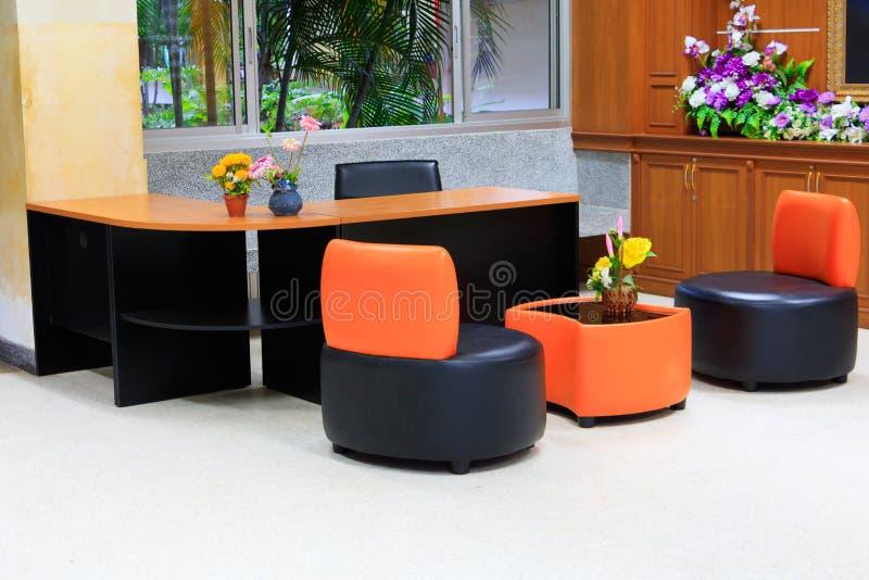 Schwarzer lederner Sofastuhl Die orange Rückenlehne- und Holztabelle, die im Bürogebäude mit Kopienraum intern ist, addieren Text stockbilder