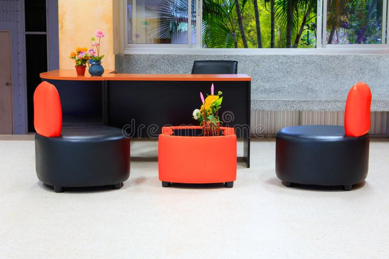 Schwarzer lederner Sofastuhl Die orange Rückenlehne- und Holztabelle, die im Bürogebäude mit Kopienraum intern ist, addieren Text lizenzfreie stockfotografie