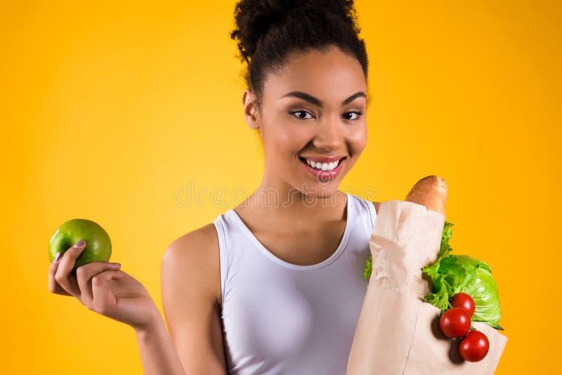 Schwarzer Mädchenholdingapfel und -lebensmittelgeschäfte lokalisiert stockfoto