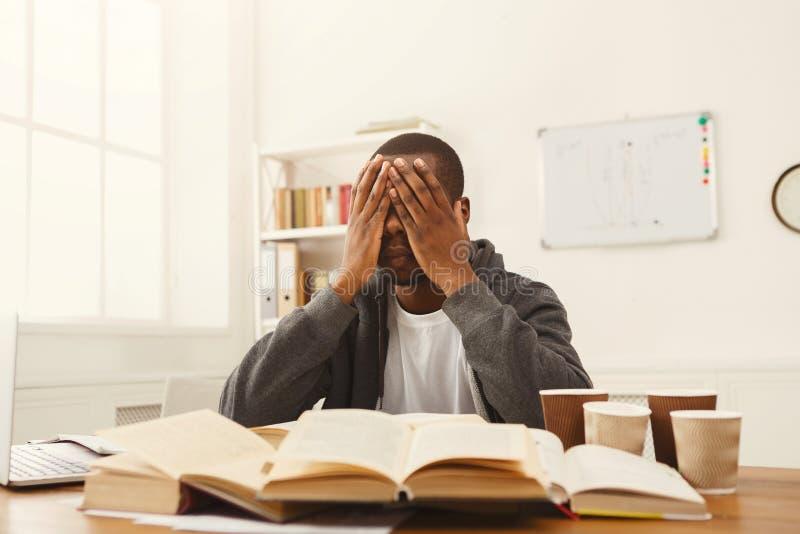 Schwarzer männlicher Student, der bei Tisch voll von den Büchern studiert lizenzfreies stockbild