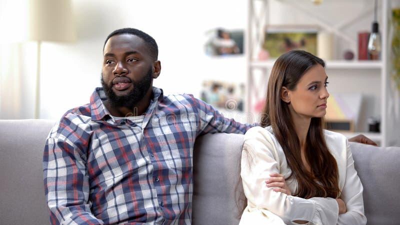 Schwarzer Mann deprimiert über den Konflikt, sitzend auf Sofa mit beleidigter Freundin lizenzfreie stockfotografie