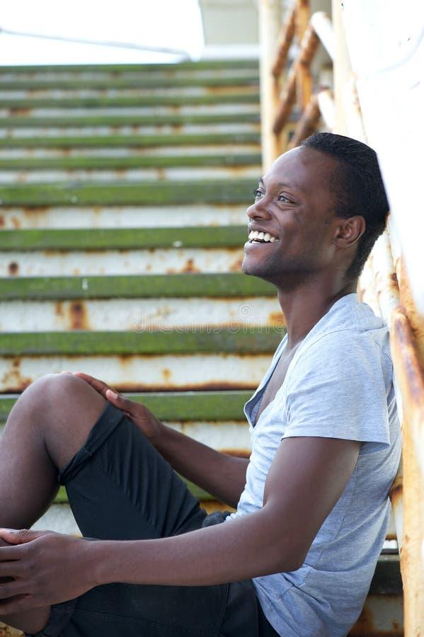 Schwarzer Mann, der draußen auf Treppe und dem Lachen sitzt stockfotografie