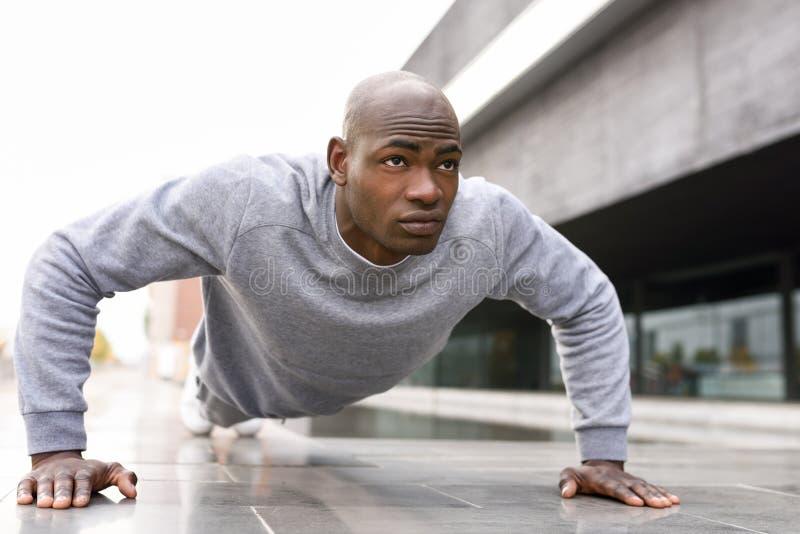 Schwarzer Mann der Eignung, den das Trainieren drücken, ups in städtischen Hintergrund stockbilder