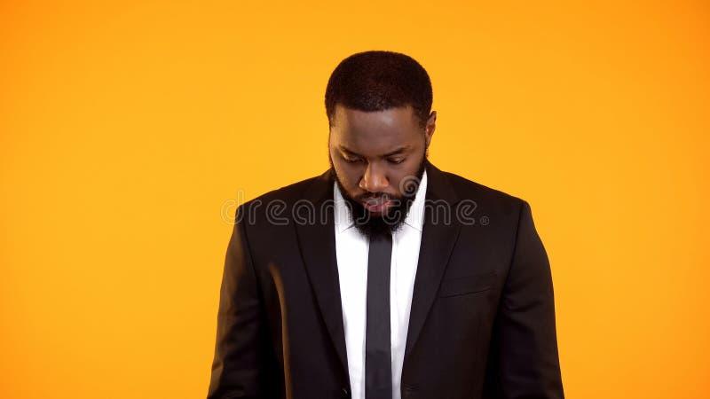 Schwarzer Mann im formalwear, das hinunter das Gefühl schuldig, denkend an Konsequenzen schaut lizenzfreies stockfoto