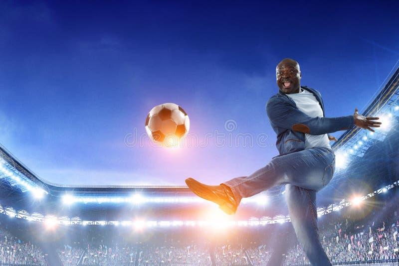 Schwarzer Mann spielt sein bestes Fu?ballspiel Gemischte Medien stockbild