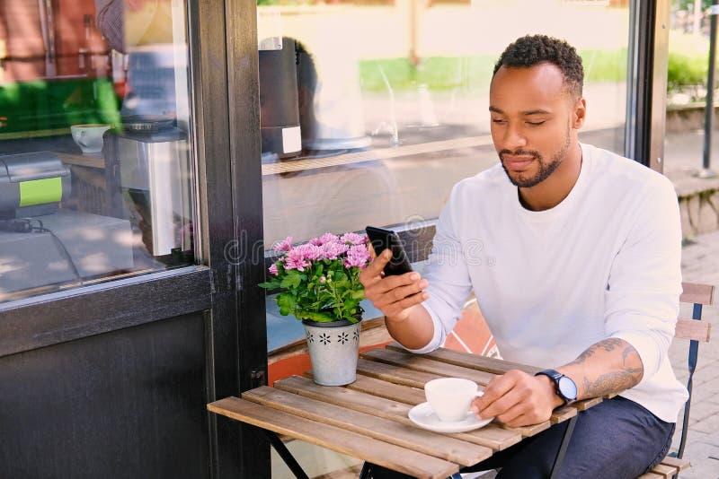 Schwarzer Mann trinkt Kaffee und mit Smartphone lizenzfreies stockbild