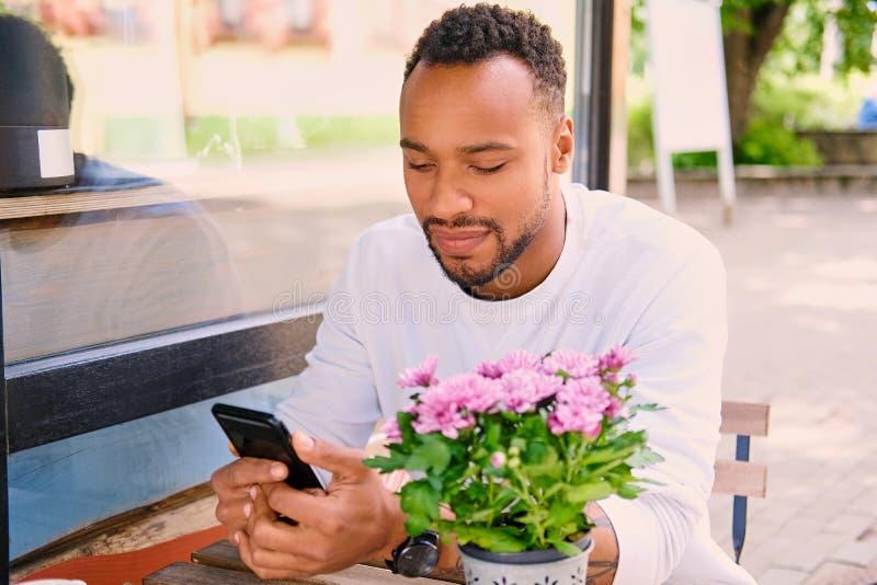 Schwarzer Mann trinkt Kaffee und mit Smartphone stockfoto
