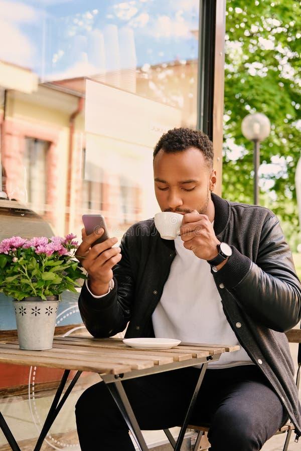 Schwarzer Mann trinkt Kaffee und mit Smartphone lizenzfreie stockbilder