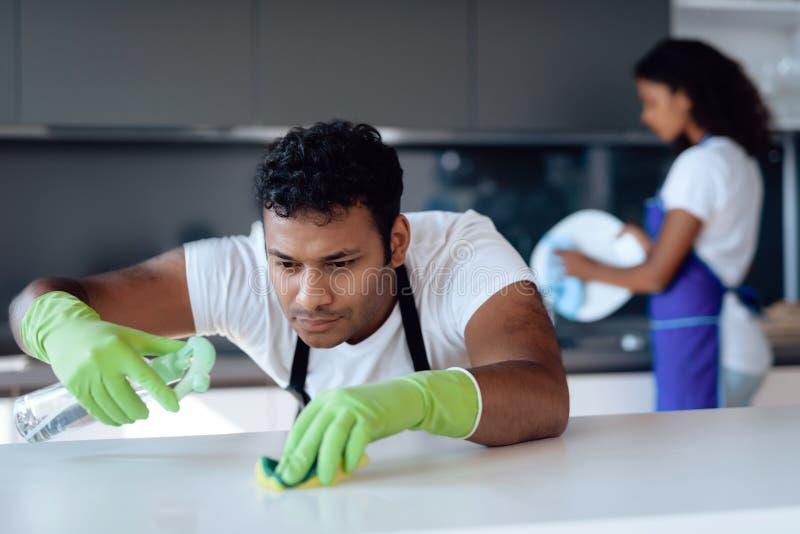 Schwarzer Mann und Frau in der Küche zu Hause Sie säubern in die Küche Ein Mann wäscht den Countertop mit Reinigungsmittel stockfotografie