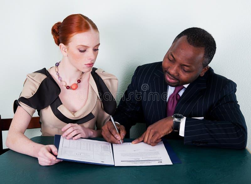 Schwarzer Mann und Redheadmädchen mit Unterlagen stockfotos