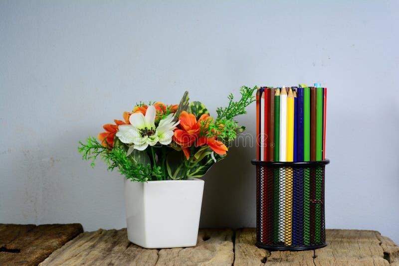 schwarzer Metallbleistiftkasten und weißer Vase auf altem Holztisch lizenzfreie stockfotografie