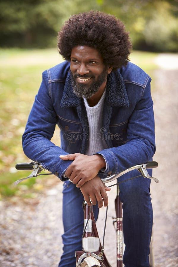 Schwarzer mittlerer gealterter Mann, der auf einem Fahrrad in einem Park, lehnend auf den oben lächelnden Lenkstangen, Vorderansi stockfoto