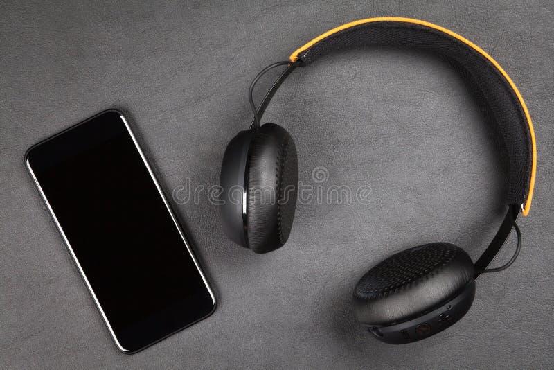 Schwarzer moderner Smartphone und Kopfhörer stockfotografie