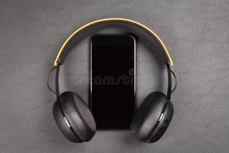 Schwarzer moderner Smartphone und Kopfhörer lizenzfreie stockbilder
