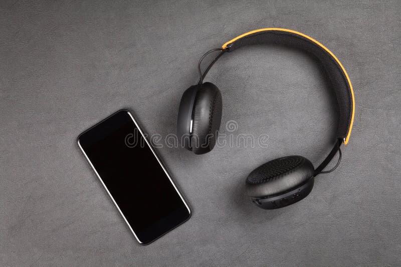 Schwarzer moderner Smartphone und Kopfhörer lizenzfreie stockfotografie