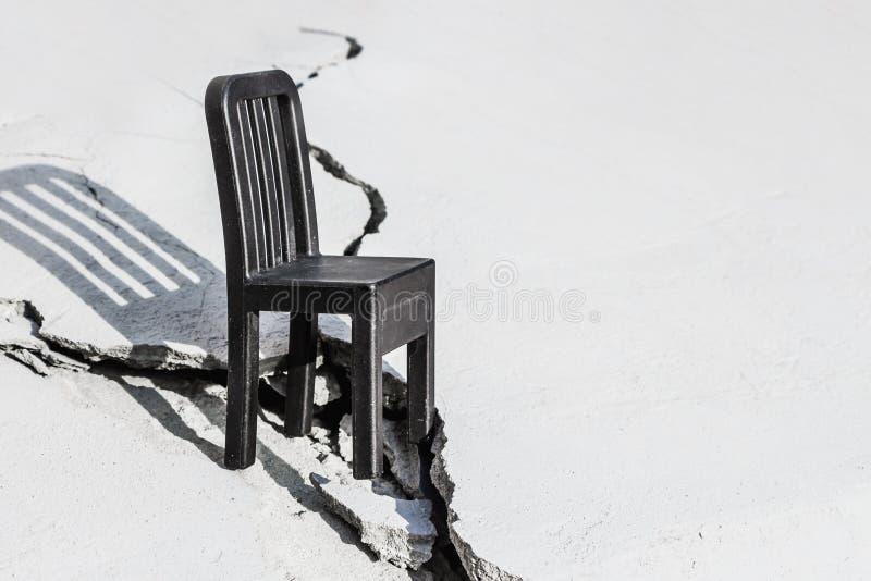 Schwarzer Plastikspielzeug-Sessel mit Schatten steht auf einer weißen Oberfläche mit Riss stockfotos
