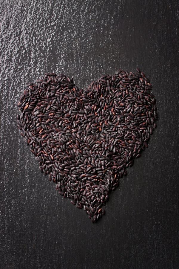 Schwarzer Reis in der Herzform auf einem schwarzen Steinhintergrund mit Wassertröpfchen lizenzfreie stockbilder