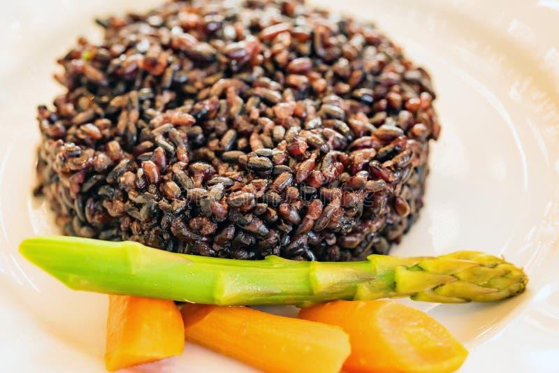Schwarzer Reis mit Gemüse auf weißem Plattenabschluß stockfoto